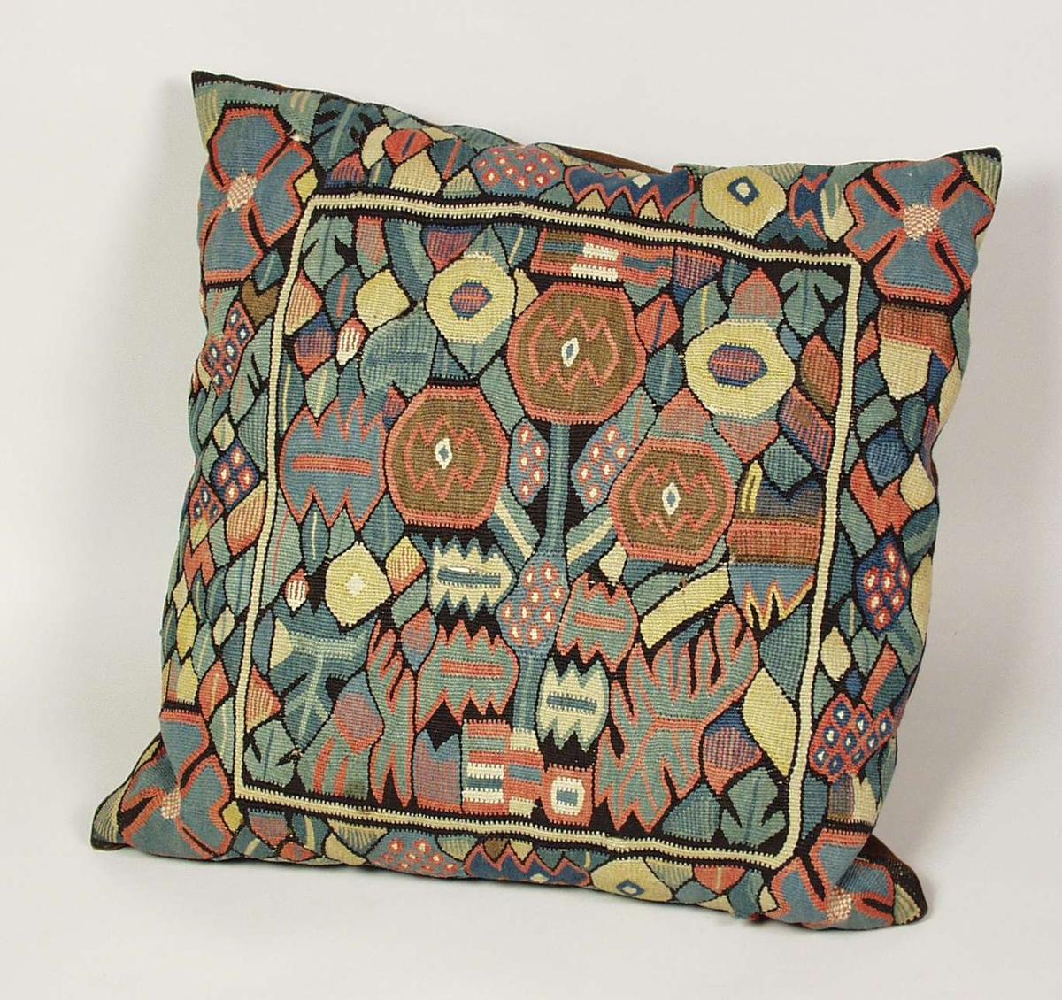Sofapute i billedvev med Gerhard Munthe-lignende mønster.Det er brukt plantefarger. Det er enkelte hull i billedveven. Baksiden er brun.