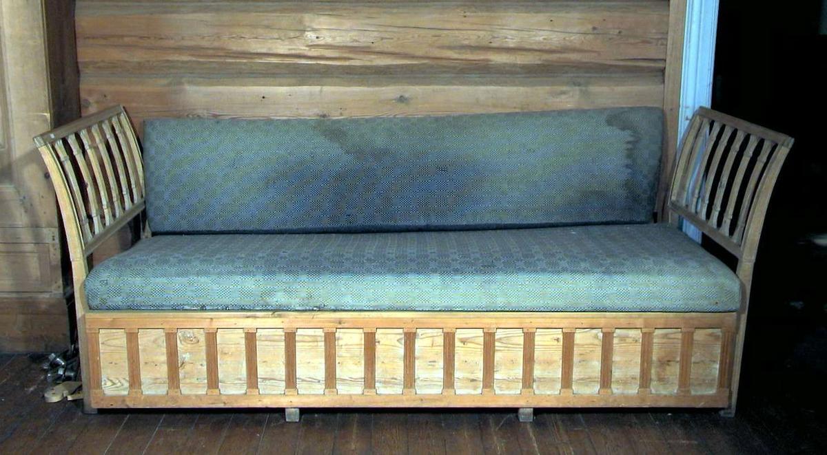 Trehvit sofa med stoppet sete og ryggpute. Vangene er i tre. Det er skuff under setet. Stoffet er blått og hvitt i en rute/stripe effekt. Det er slitt og flekkete.