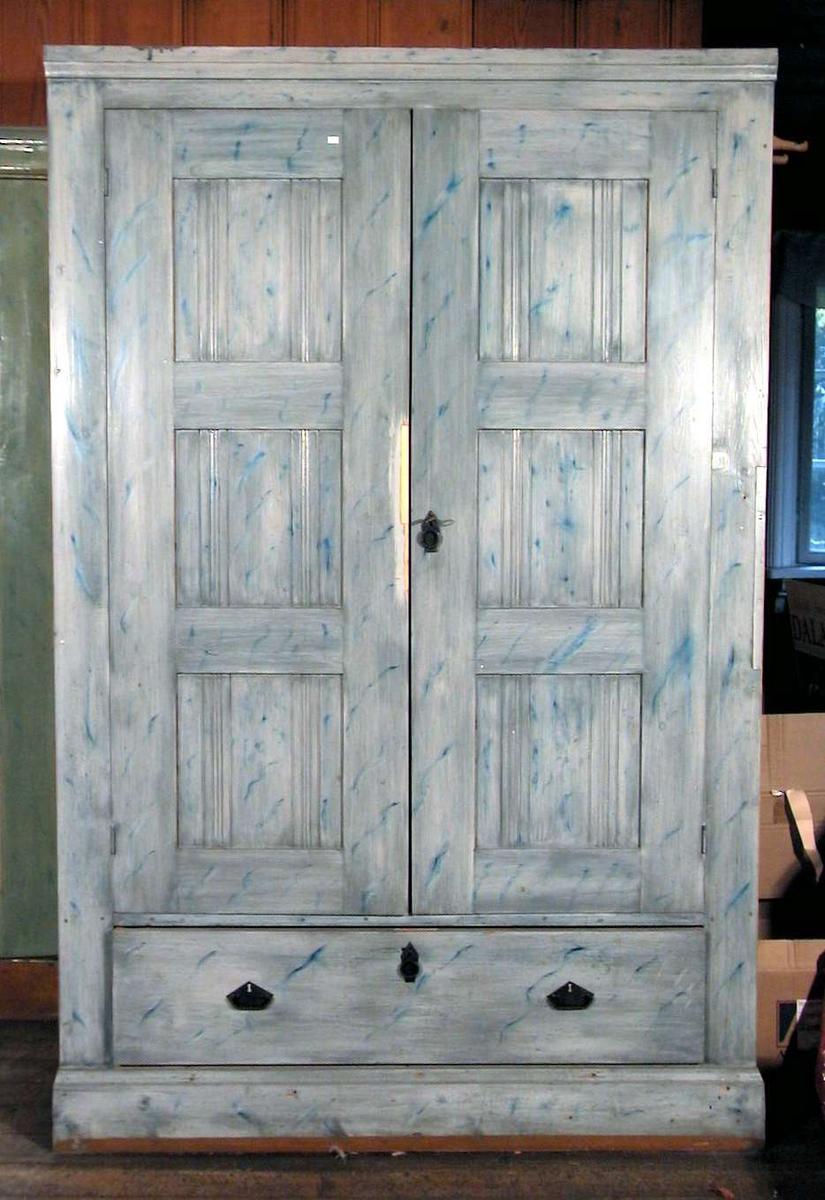 Klesskap med to dører og en stor skuff. Skapet har front malt i blågrønt. Sidene er huntonittplater.