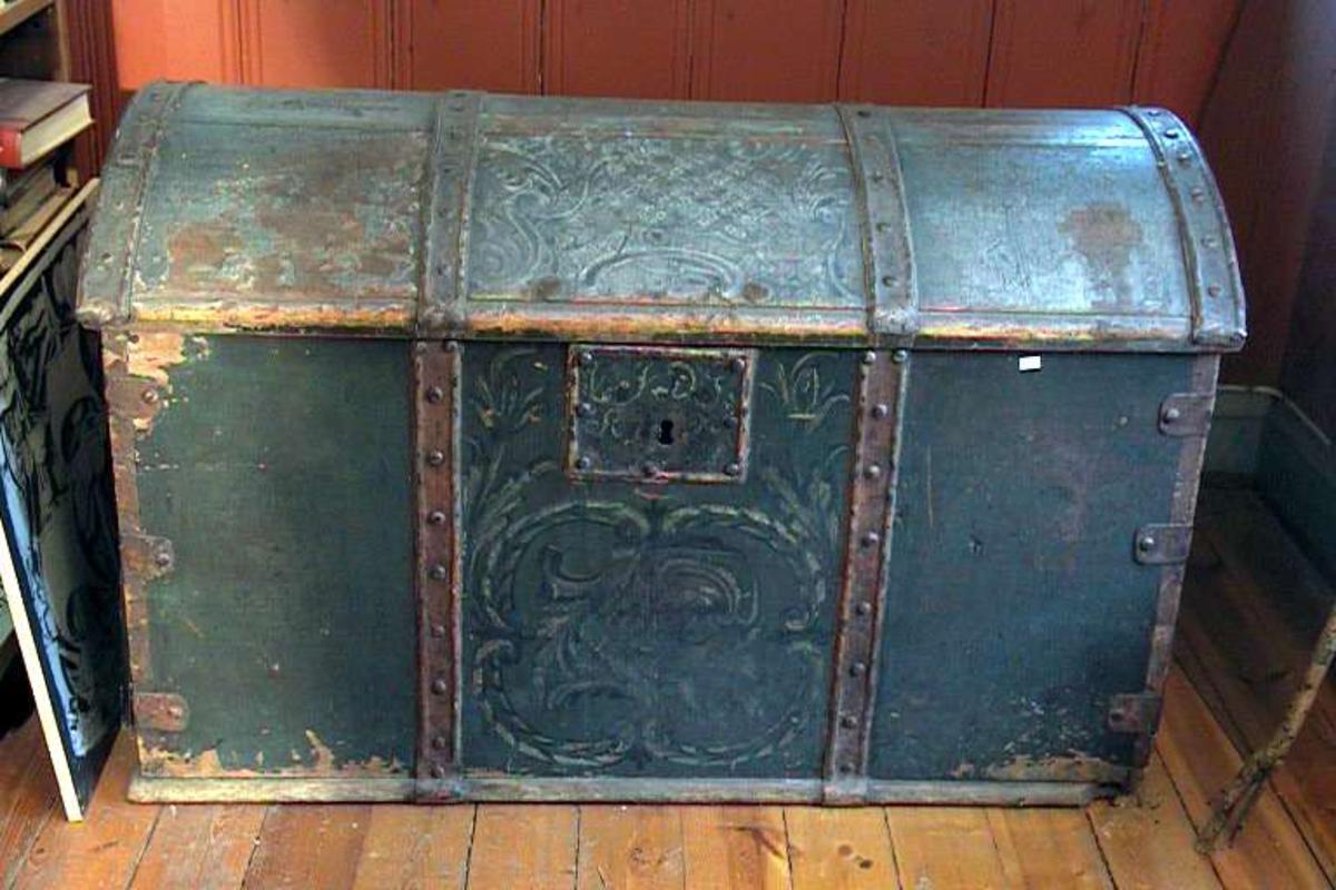 Kiste av tre med beslag og hengsler av jern. Den er malt grønnblå. Malingen er avslitt. Kisten er dekorert. Innvendig er det sort/beige dekor på gråhvitt. Det er en 'hylle' innvendig. Låsen er defekt, den ligger løs. Treverket mangler i et hjørne.