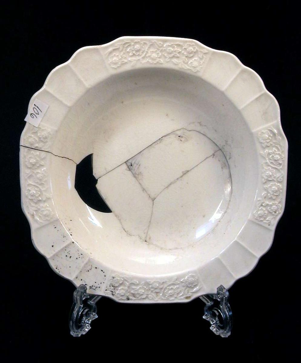 Elfenbenshvit glasert dyp tallerken med dekor i relieff.