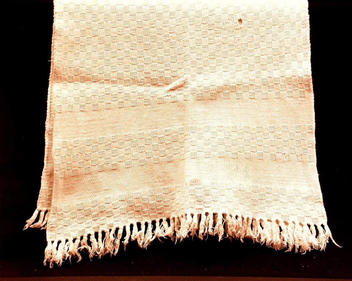 Hvitt håndkle, strikket med tverrborder og sjakkruter. Påsatte frynser i hver ende. Bendelbånd hempe. Alt i bomull.