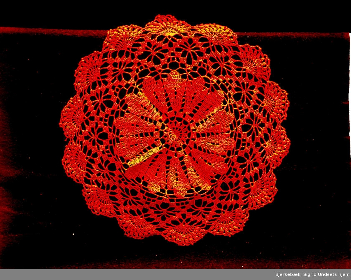Rød heklet brikke med midtrosett og tunget ytterkant. Høyrødt mercerisert bomullsgarn av perlegarnstypen.