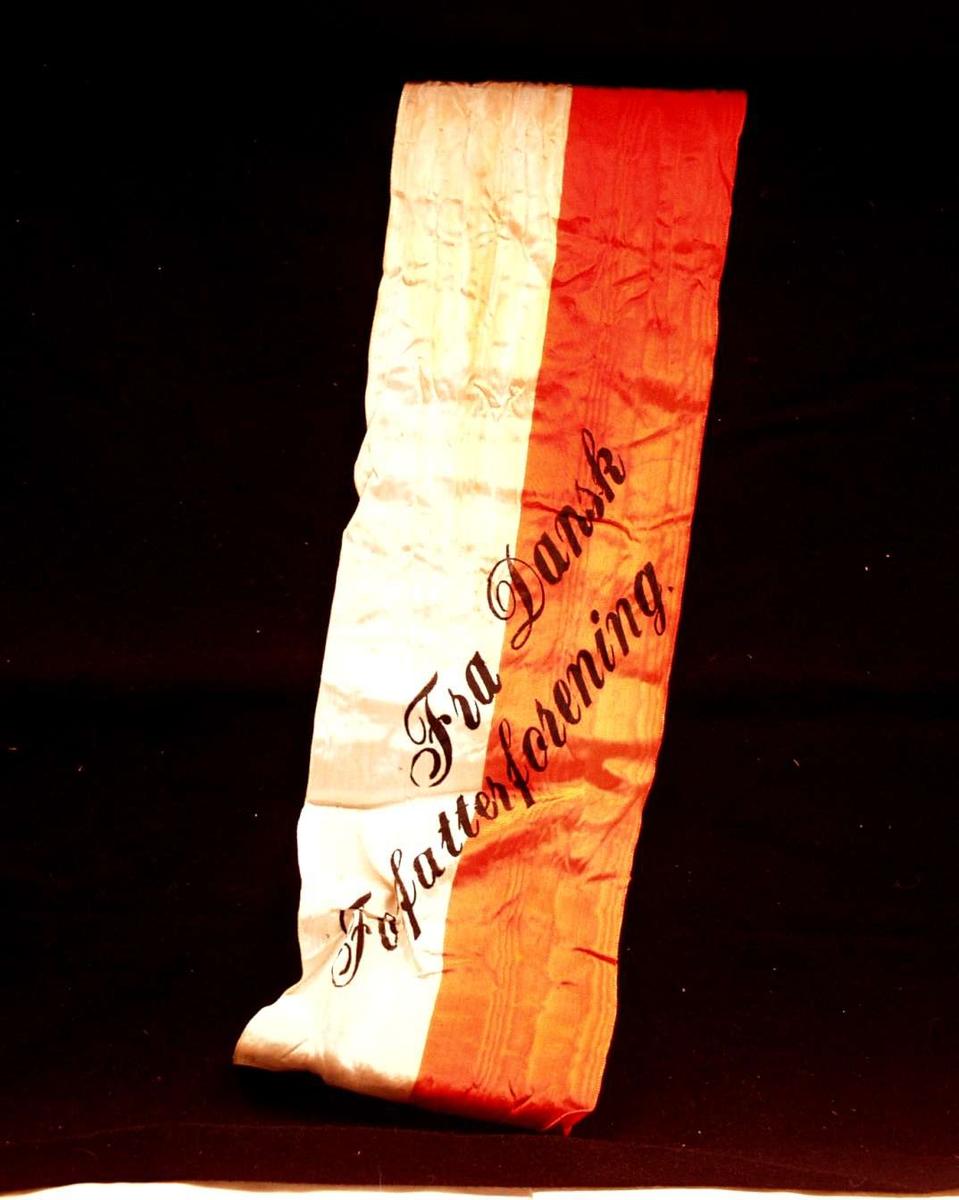 Bånd i rød og hvit silke. Båndet er delt i to, men den ene delen mangler. På båndet står det: Fra Dansk Forfatterforening.
