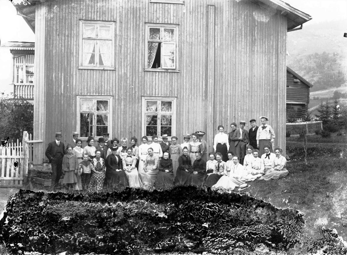 Gunstads gjester  24/7 - 03. Gruppebilde, hus i bakgrunnen