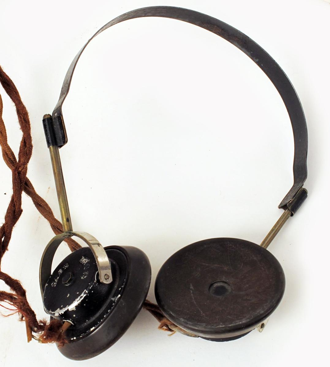 Elektrisk ovn med innmontert (kamuflert) radio og øretelefoner, innstilt på kortbølge 25, London under krigen  1940 - 45, for avlytting av de norske sendinger.    a) Sortmalt  jernblikk.    Sortmalt rektangulær høy smal kasse med tre rader ,  Rull øverst og flatt topplokk, på fire ben av galvaniserte  plater, som fortsetter opp langs ovnens  hjørner og ender i lokkets hjørner. En ledning  stikker ut nederst i den ene kortende og inn i  bunnen.    b) Øretelefon med to sorte øreklaffer og sort hode  feste. På øreklaffene: Telefunken E. H. 555.  Lang slitt brun ledning, lappet med rosa plaster.