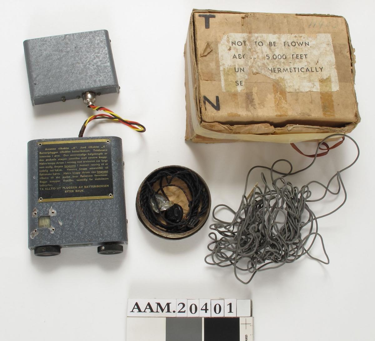 """Radiomottaker,  kalt   Sweetheart"""",   med øretelefoner, antenne og batteriboks.   a) Radiomottaker.   Metall,  malt militærgrått med """"ruflet"""" mønster.   Flat rektang. boks, på den ene side med avrundede langsider.   H. u.knapper 12,2. Total H. 13,3. B. 11. Dybde 3.  I den ene kortside to stilleknapper/hjul, mellom dem metallskilt med nr. 14724. felt med skala, i øvre del stor sort tekstfelt med tekst i gull med bruksanvisni  b) Antenneboks,   metall,  gråmalt.   H. 10,5. B. 7,8. Dybde 2,5.  Lite sort stempel: 191. Tom for batterier.    c) Antenne.  grå, tynn ledning, flere meter. med Gummibelagt med stålwire inni.    d) Rund metalldåse med flatt lokk.   Diam. 8,2.  Inni denne ligger to små øretelefoner med sort snodd ledning.  Selve øreapparatet er av sort bakelitt og klart glass. Noe rødbrun lakk  i tuppene, litt på ledningen og inni kanten av lokket. Merket:   Pat. Pend. F 4, og Brush.    e) Pappeske.   H. 7,5. L. 19,5. B. ca. 15.  Th. på lokket med blå blyant: 11403. Hvit etikett med sort  tekst:   Not to be flown above 5,000 Feet Un.hermetically Se.""""  (avrevet)."""