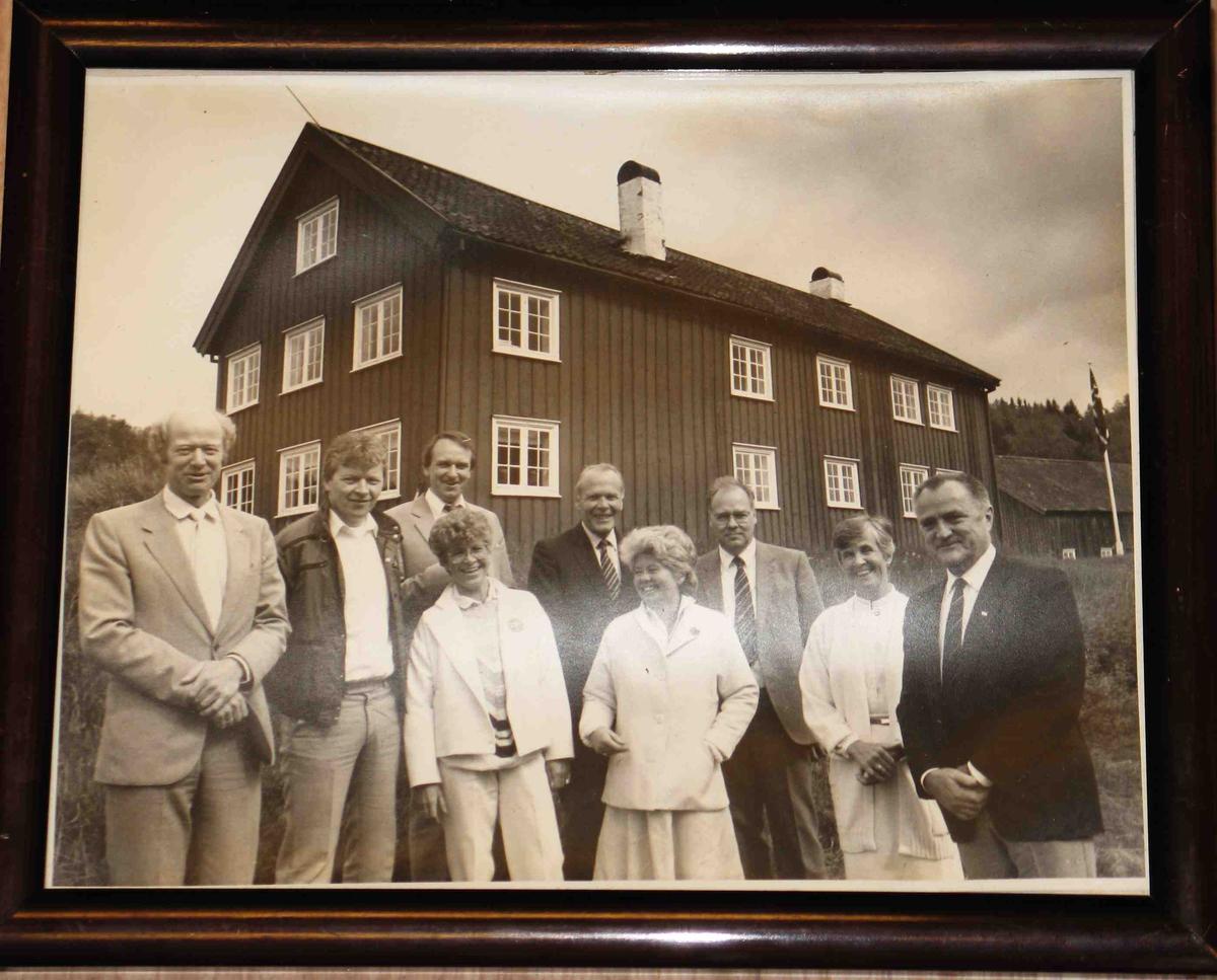 Gruppeportrett, fylkestinget 1987, samlet på Østre Angelstad i Tvedestrand kommune i anledning av at formannskapslovene var 150 år. I 1837 ble  det første fylkestinget avholdt i Aust-Agder i bygningen i bakgrunnen. 9 kjente fylkespolitikere fra Aust-Agder er avbildet. I bakgrunnen våningshuset som da var restaurert av Aust-Agder-Museet etter at museet overtok bygningene 10 år tidligere. Lengst bak t.h. skimtes flaggstangen med flagget og låven.