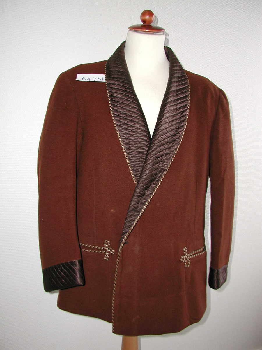 Ulljakke med vatterte silkeoppslag på krave og ermer. Snorer som dekor langs kanten og rundt lommene.