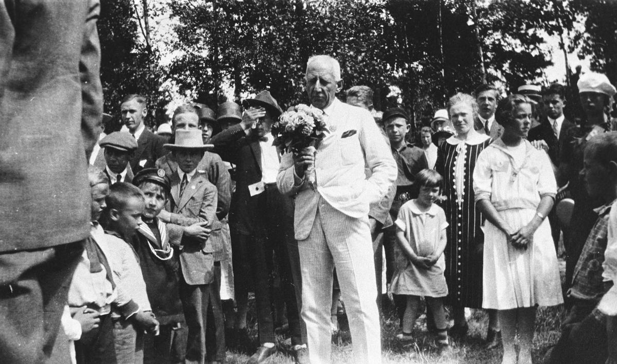Roald Amundsen med blomster midt i en forsamling.