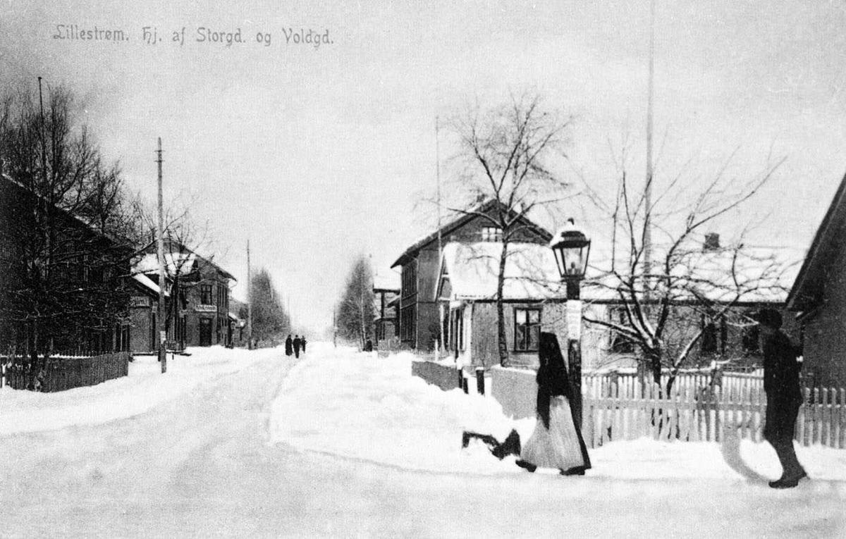 Lillestrøm. hj. af Storgd. og Voldgd.  Postkortfoto Vinterbilde. En gatelykt i krysset, og en stolperekke langs Storgt.