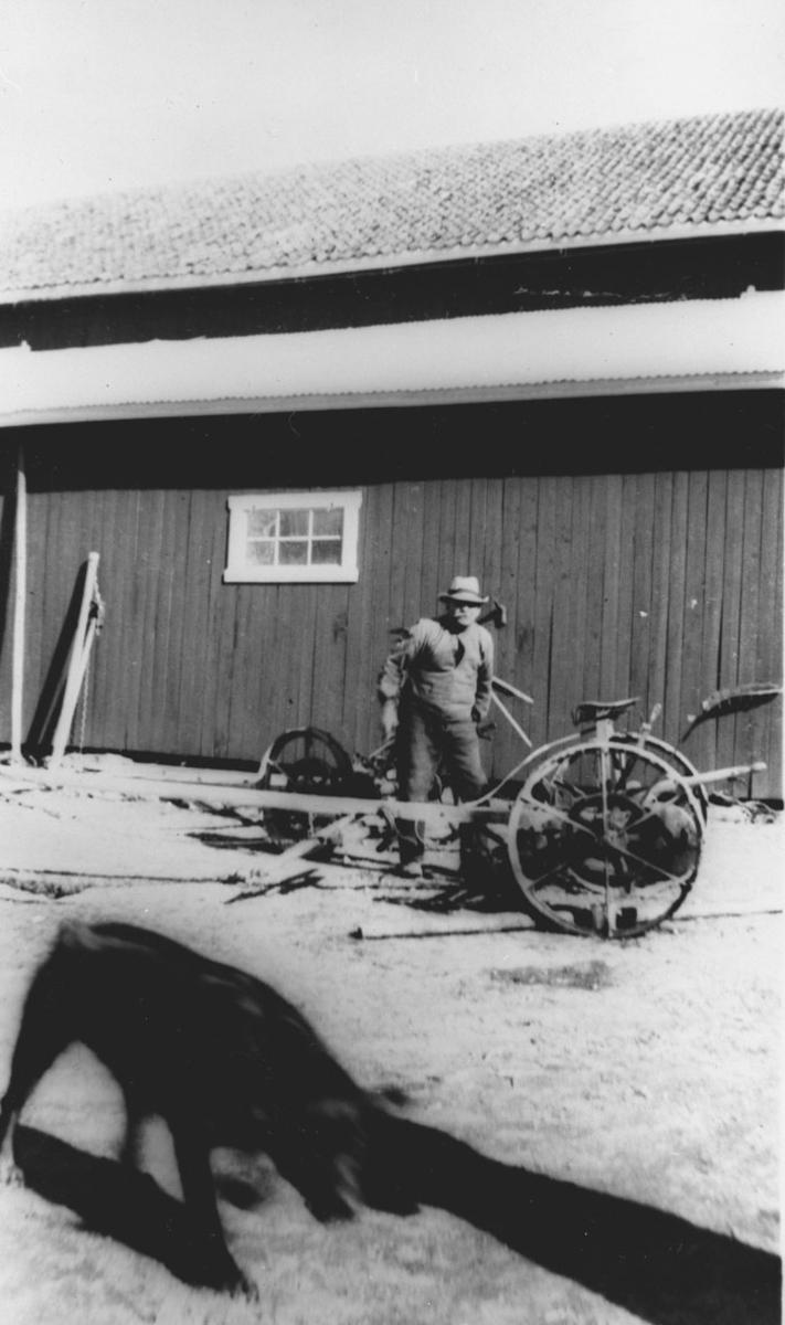 Sigvart Lauten reparerer slåmaskinen.