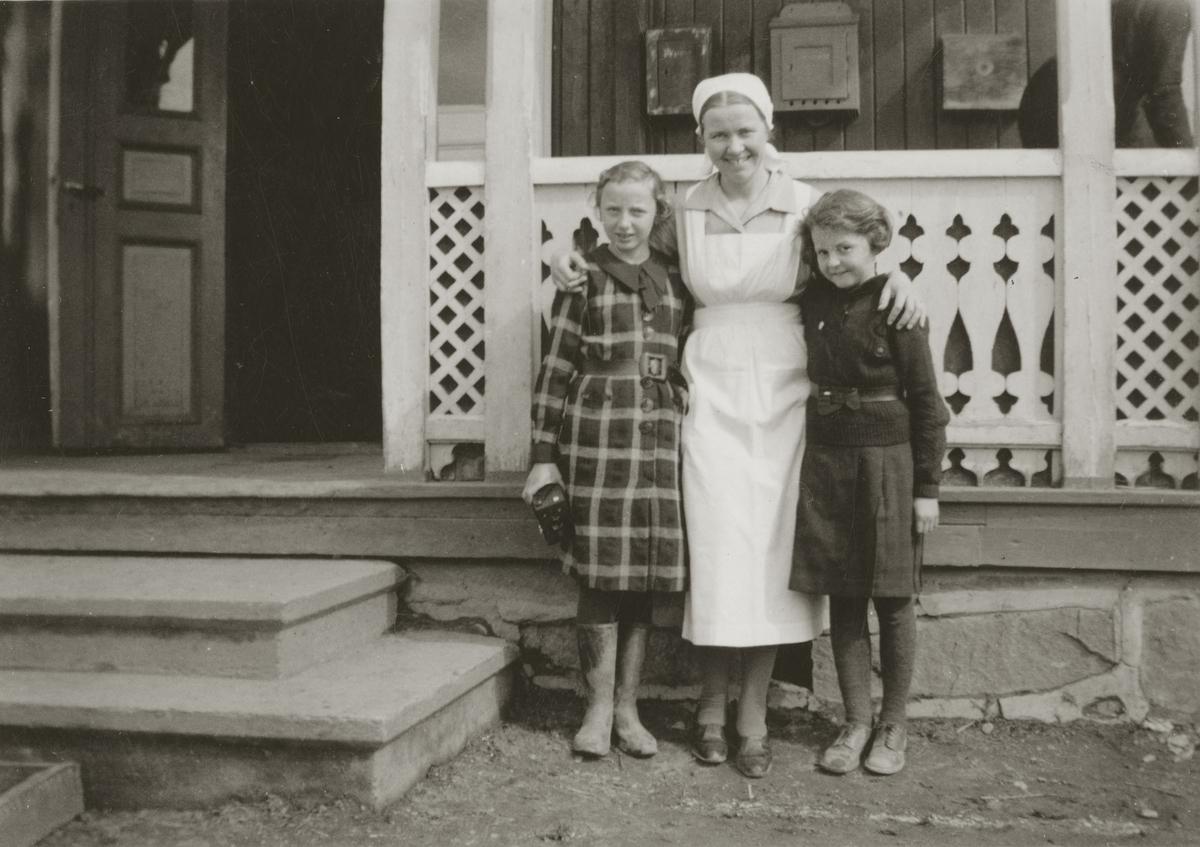 Frk. Løvstad i hvitt forkle/arbeids uniform. Åse Moe Holt til venstre med foto apparat, Liv Frogner helt til høyre. Ved inngangen til Ullinshof skole.
