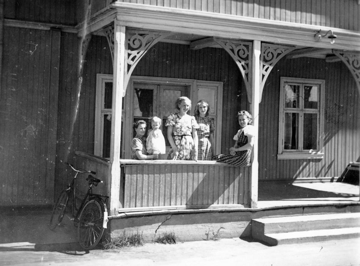 Gruppe barn og voksene samlet på verandaen til Hotel Køgler.