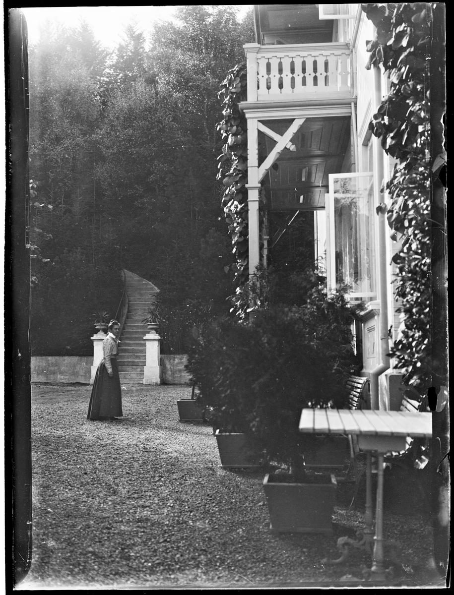 Skodsborg, Danmark. Julie Mathiesen foran et hus. En trapp i bakgrunnen fører opp mellom trærne.