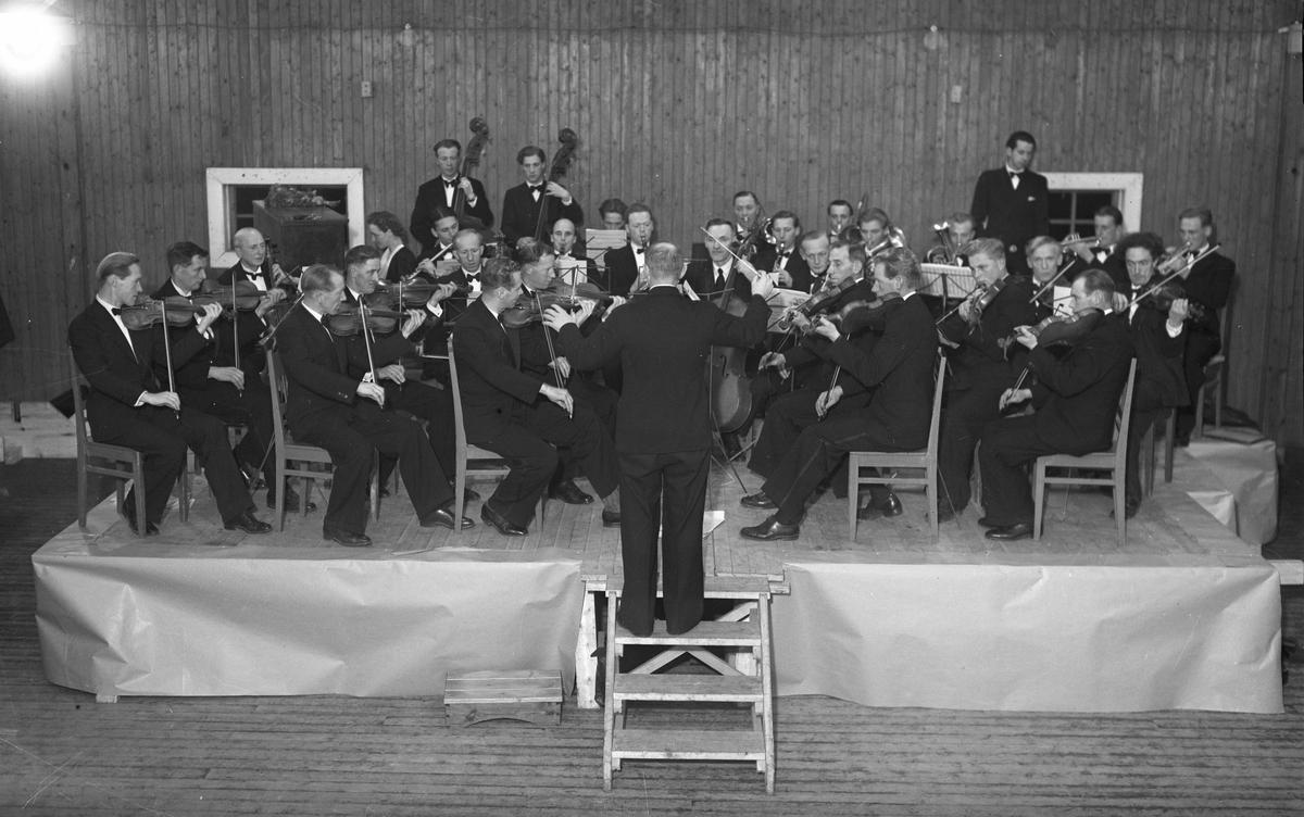 Symfoniorkester. Vi ser Alex Lindahl, Ivar Bjørn, Jens Christian Aas, Ivan Grue, Henrik Grimeland? og Kåre Ruud på bildet. Dirigent: Magne Høyberget. Kan være i gymsalen på Landsgymnaset – like etter krigen.