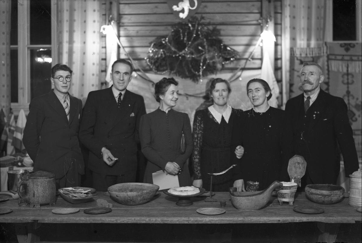 Menn og kvinner ved et bord med treskjæringsprodukter. Redaktør i Eidsvoll Blad Erling Grieg nr. 2 fra venstre.