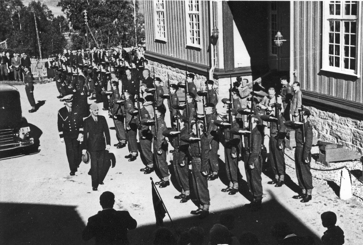 Kong Haakon inspiserer soldater ved Eidsvollbygningen. Det er usikkert i hvilken anledning. Like etter krigen – se uniformene.