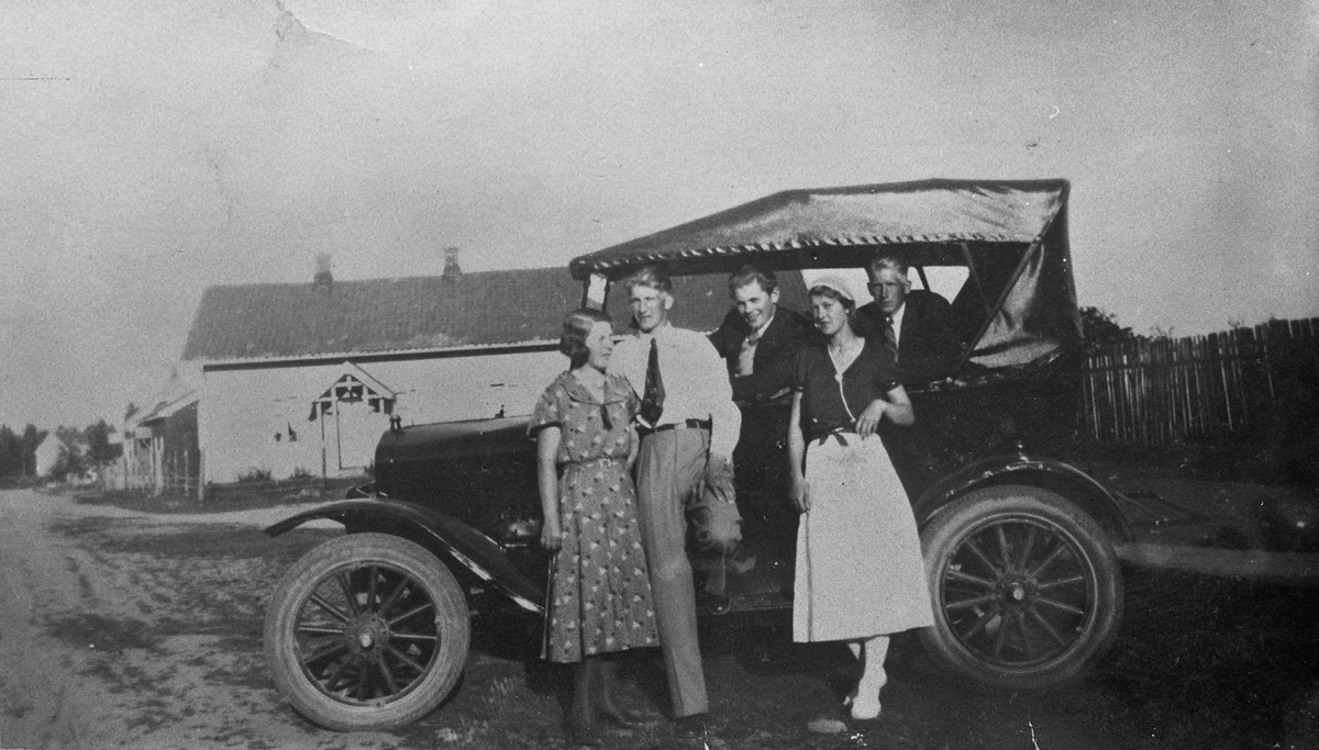 Kvinner og menn ved en bil av 1920-40 talls modell.