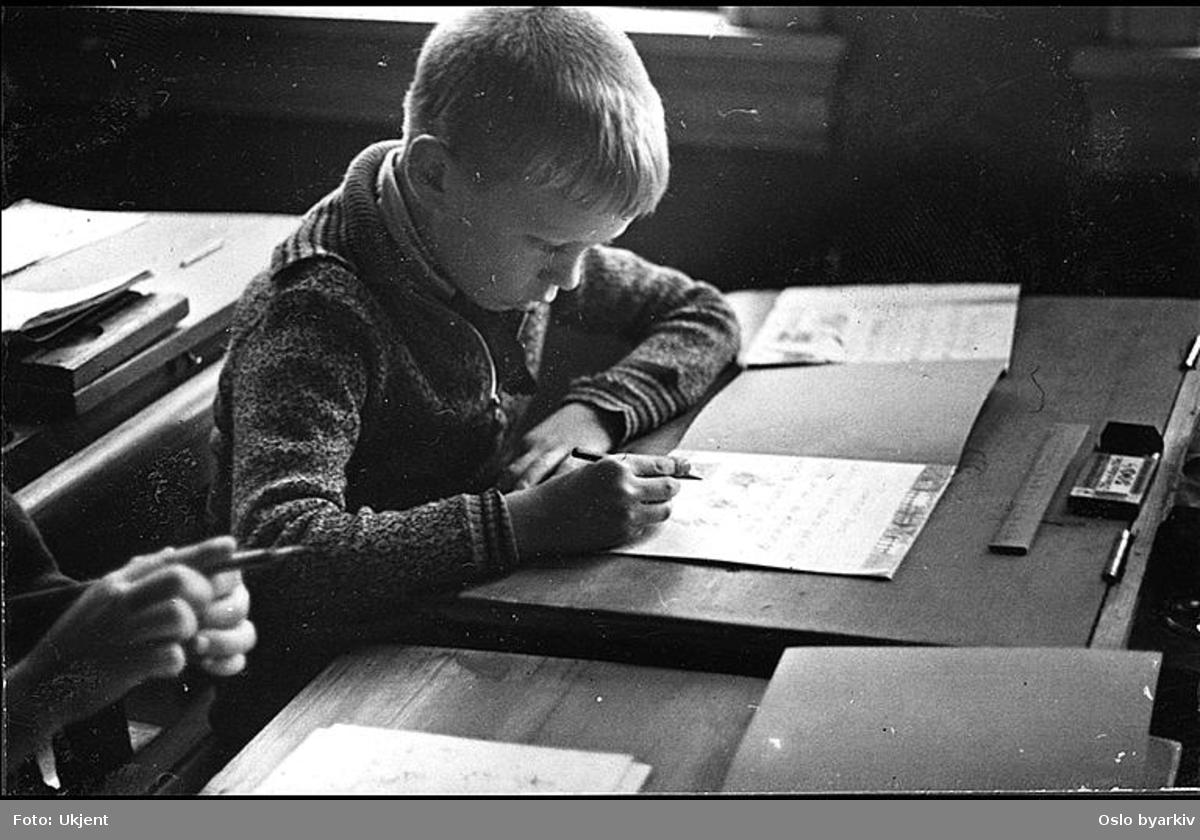 """Gutt i dyp konsentrasjon over mattematikkoppgave. Albumtittel: """"Sofienberg skole femti år - første september 1933."""""""