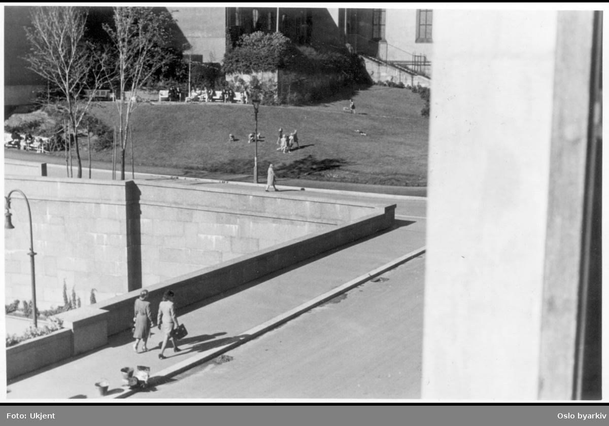 Bildet tatt i fra Hovedbrannstasjonen (Arne Garborgs plass 1) mot Margaretakyrkan. To kvinner spasserende i Grubbegata over brovelvet til Henrik ibsens gate (nå Hammersborggata). Barn leker på grøntområdet utenfor kirken. Mennesker sittende på hvite benker.