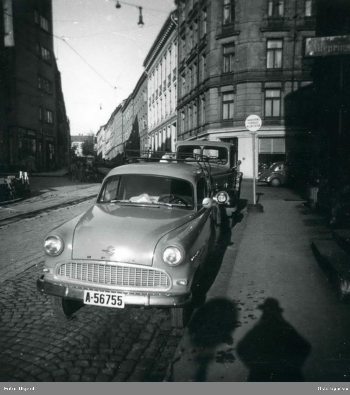 Trikketrase i brosteinsbelagt gate. Sannsynligvis Welhavens gate med Hegdehaugsveien opp til venstre. Parkert bil (Opel) og lastebil.