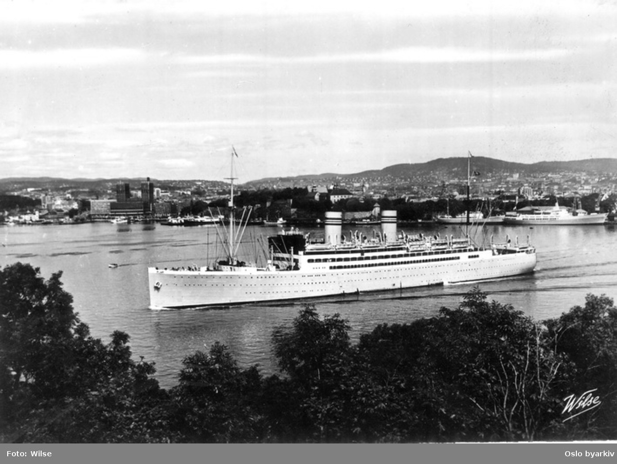 Dampskip, muligens DS Stavangerfjord, amerikabåt på utgående fra Vippetangen. Rådhuset og Akershus festning i bakgrunnen. Postkort.