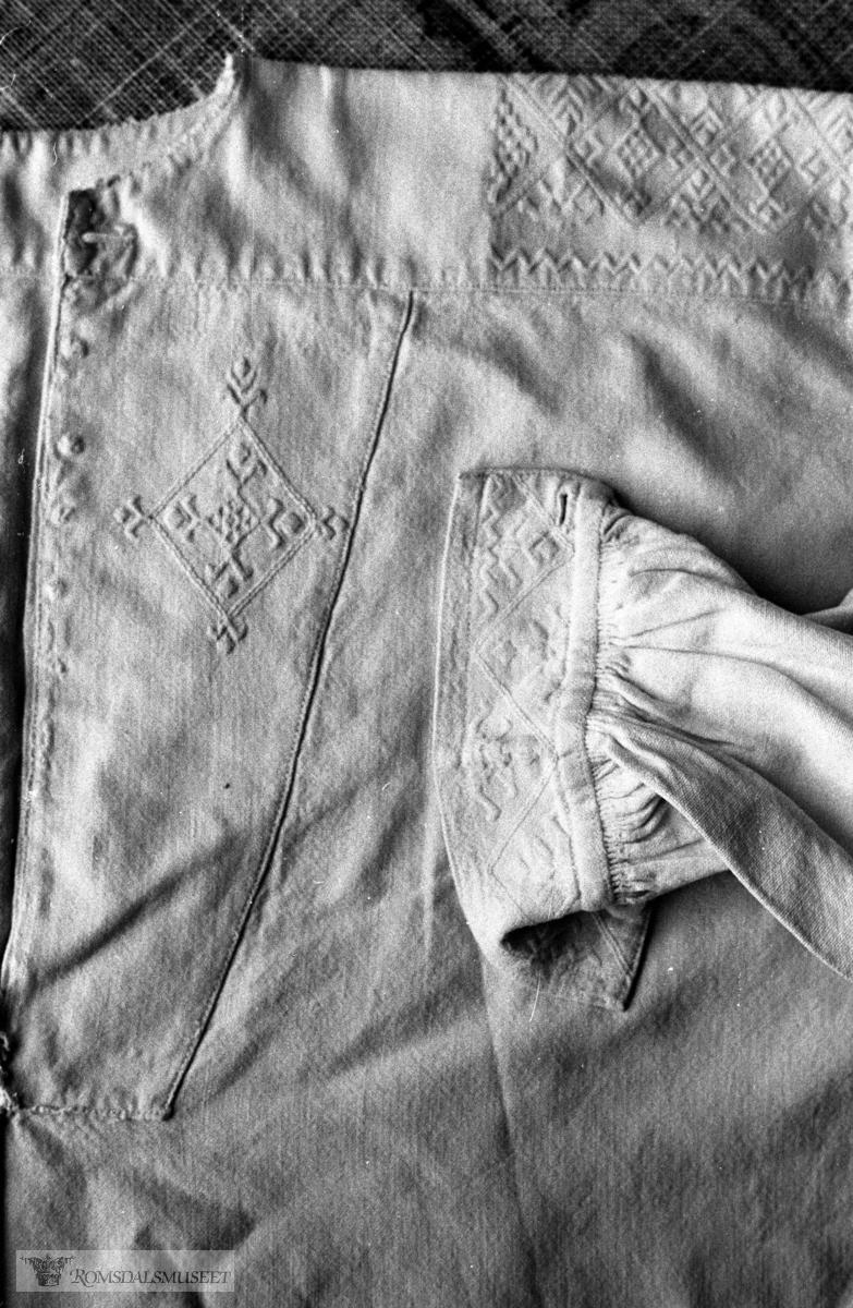 Skjorte, Laga av Ingeborg Fiksdal, fødd 1864. Mål: Armlengde 46 cm, høgde, skulder 48 cm, Vidde, nede 55 cm. Sjå også Bjørn Austigard si feltbok for 1980 side 176. Skjorta har teljesaum, holsaum og flatsaum i kombinasjon.