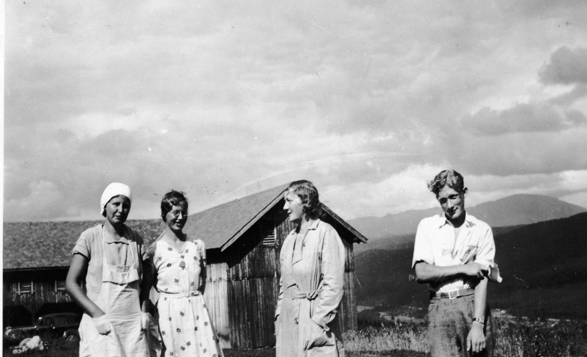 Gruppebilde,forkle,kjole,skjorte og låve. Frå v.Margit Raunedokken,Birgit Raunedokken,dei andre er ukjent.