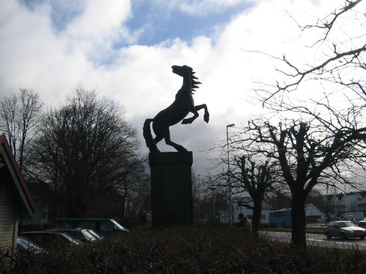 Sokkel av granitt med hest i bronse ca. 2 m. høy. Sokkel 4m høy, B 1,4m. D 1,1m.