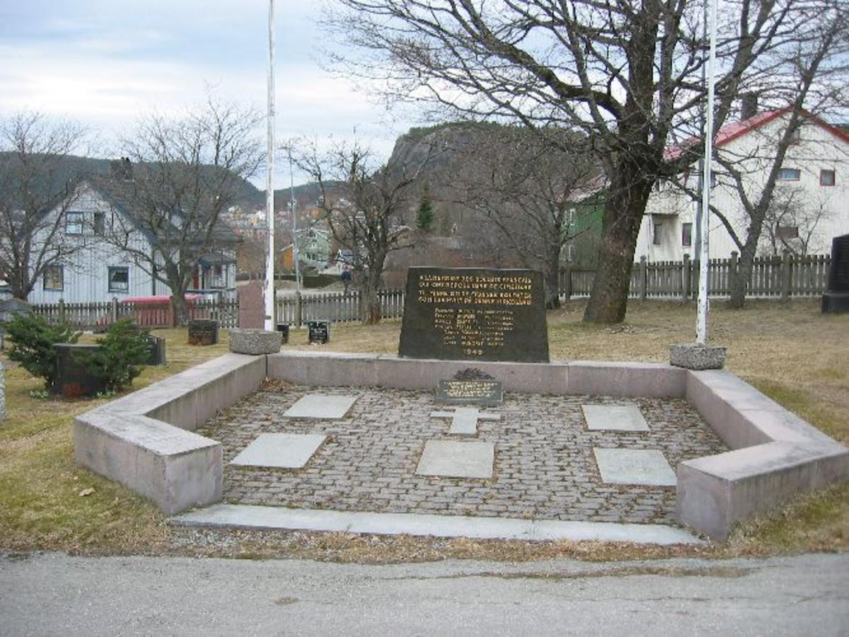 Rektangulær minnestein med syv navn. Fem liggende steinkors med navn, innenfor et massivt granittgjerde.