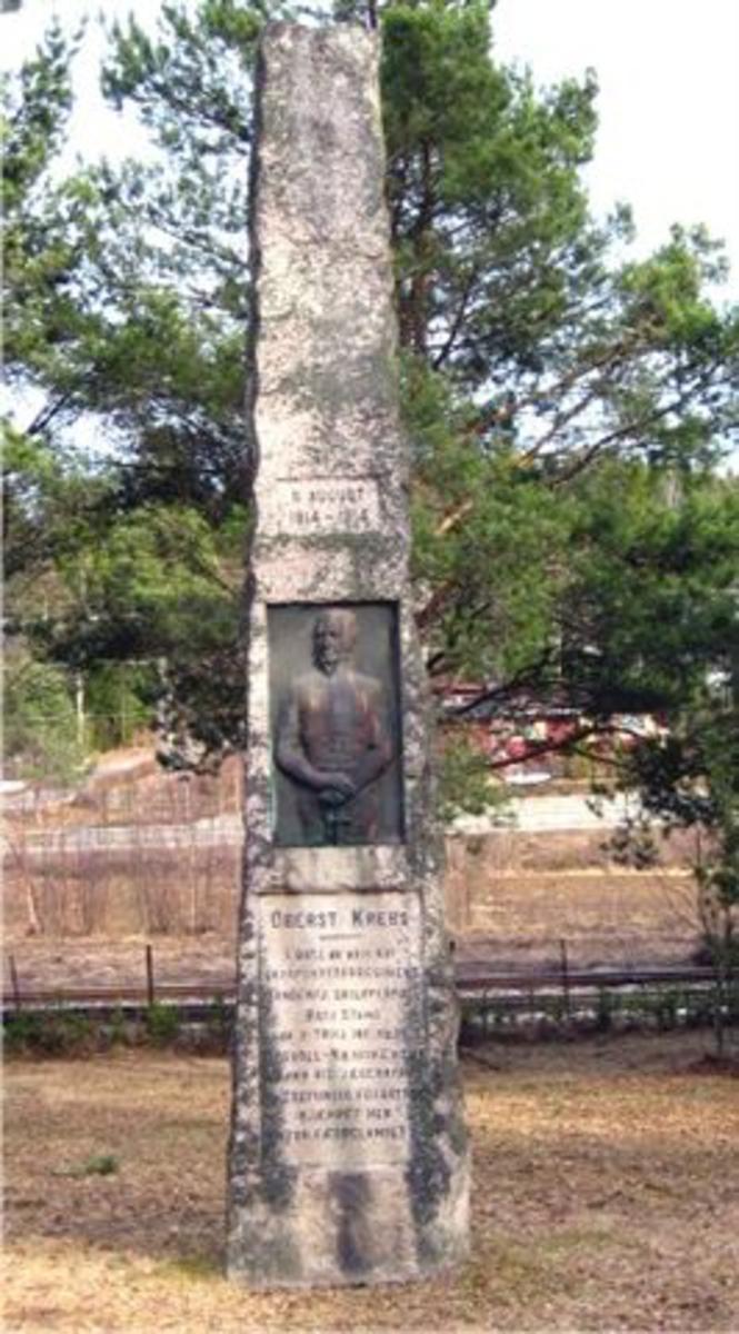 Obelisk med relieff av Krebs med tekst under og over.