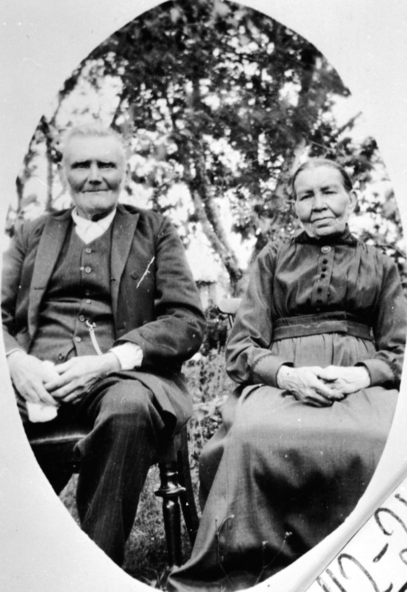 Ekteparet Johannes Akselsen og Marit Jensdatter sitter utenfor Sundby lille, Skredderbakken, Helgøya.  Marit og Johannes kalte seg Aas Sundby da de døde. Marit,født Jensdatter Robole/Robøle i Øystre Slidre 29. mar 1852, død på Hamar 9. apr 1939. Johannes, født Axelsen, østre Toten 20. jan 1844, Død 5. okt 1926 på Helgøya, Ringsaker.