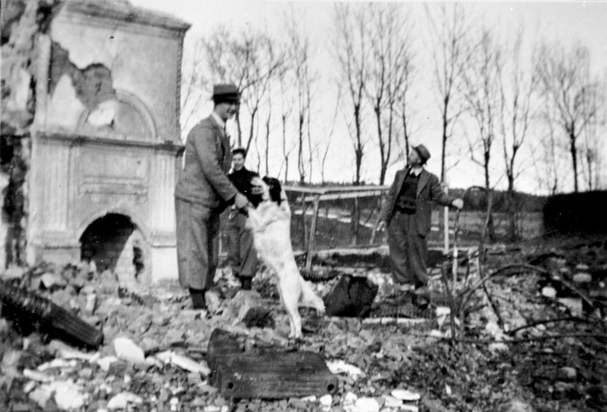 Inspeksjon av branntomta på Hovinsholm, Helgøya etter storbrannen den 20.12.1937. Gartner Kjølås til høyre og Georg Ørbekk med hunden som varslet brannen.