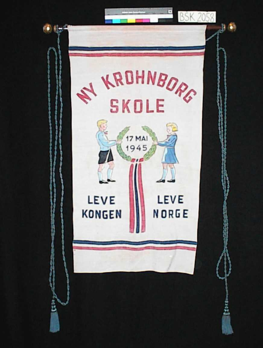 """Framside: Tekst: """"NY KROHNBORG SKOLE""""              LEVE KONGEN   LEVE NORGE              17 MAI 1945 Motiv: To barn holder i krans med sløyfe. Striper i rødt, (hvitt) og blått både oppe og nede på fanen.  Bakside: Uten motiv og mønster, kun gjennomslag fra retten."""