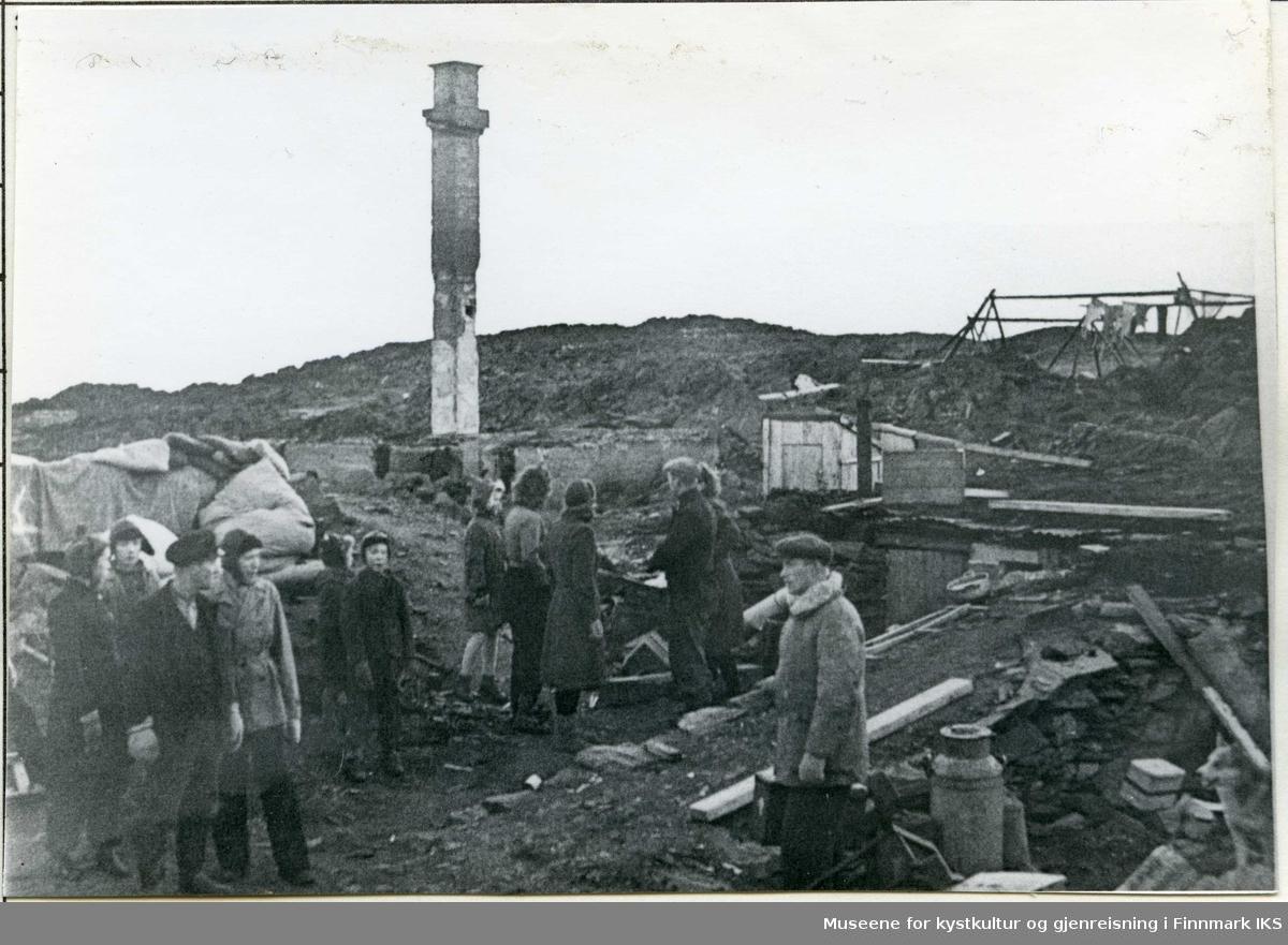 Mennesker i Gamvik leter etter husgeråd i branntomt. 1944.