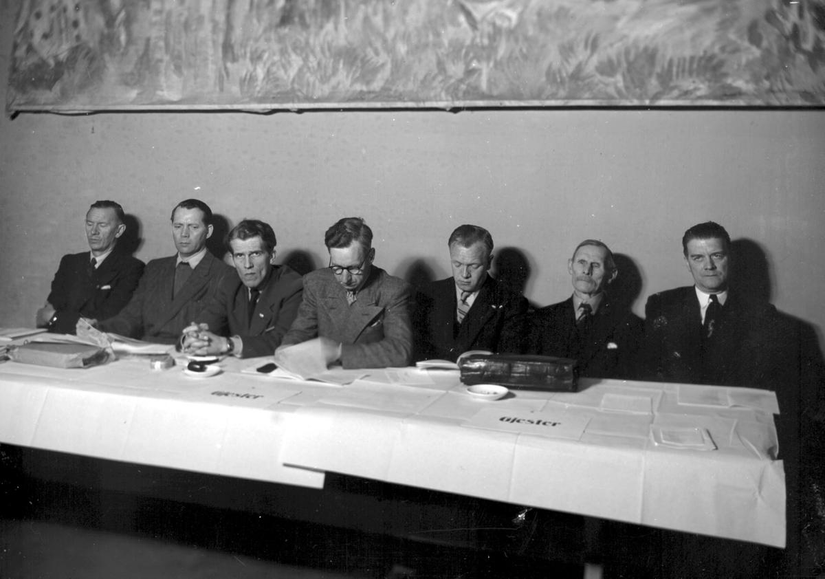 7 menn ved møtebord