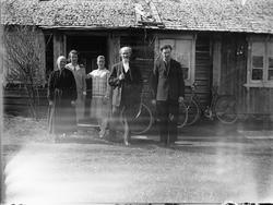 Ukjent gruppe, familie foran inngangen til et ukjent hus. To