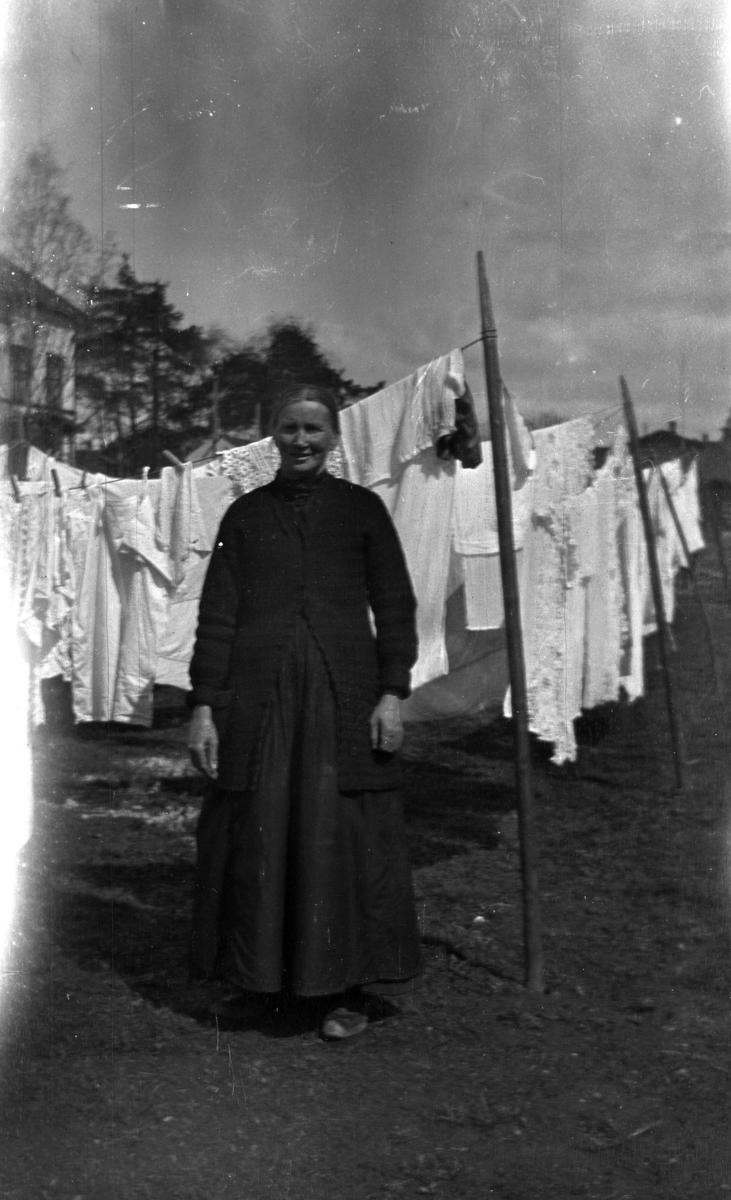 Ukjent kvinne henger opp klesvask til tørk.