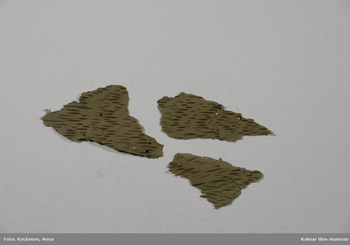 KLM 39768:6. Tapet, av papper, 3 bitar. Tryckt. Brun tapet med korta streck i mörkbrunt och ljusbrunt. Datering: 1800-tal.