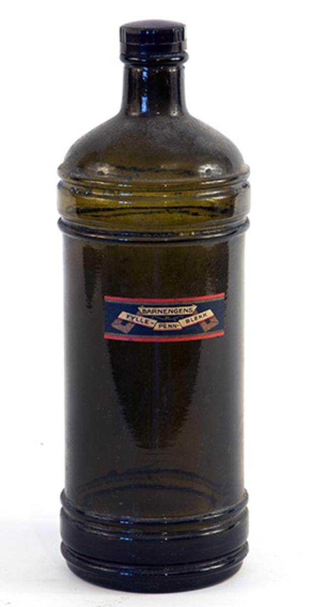 Rund flaske med skrukorkkork. Har inneholdt blekk. 4 horisontale ringer på flasken. Liten etikett; tekst Barnengens fyllepennblekk.