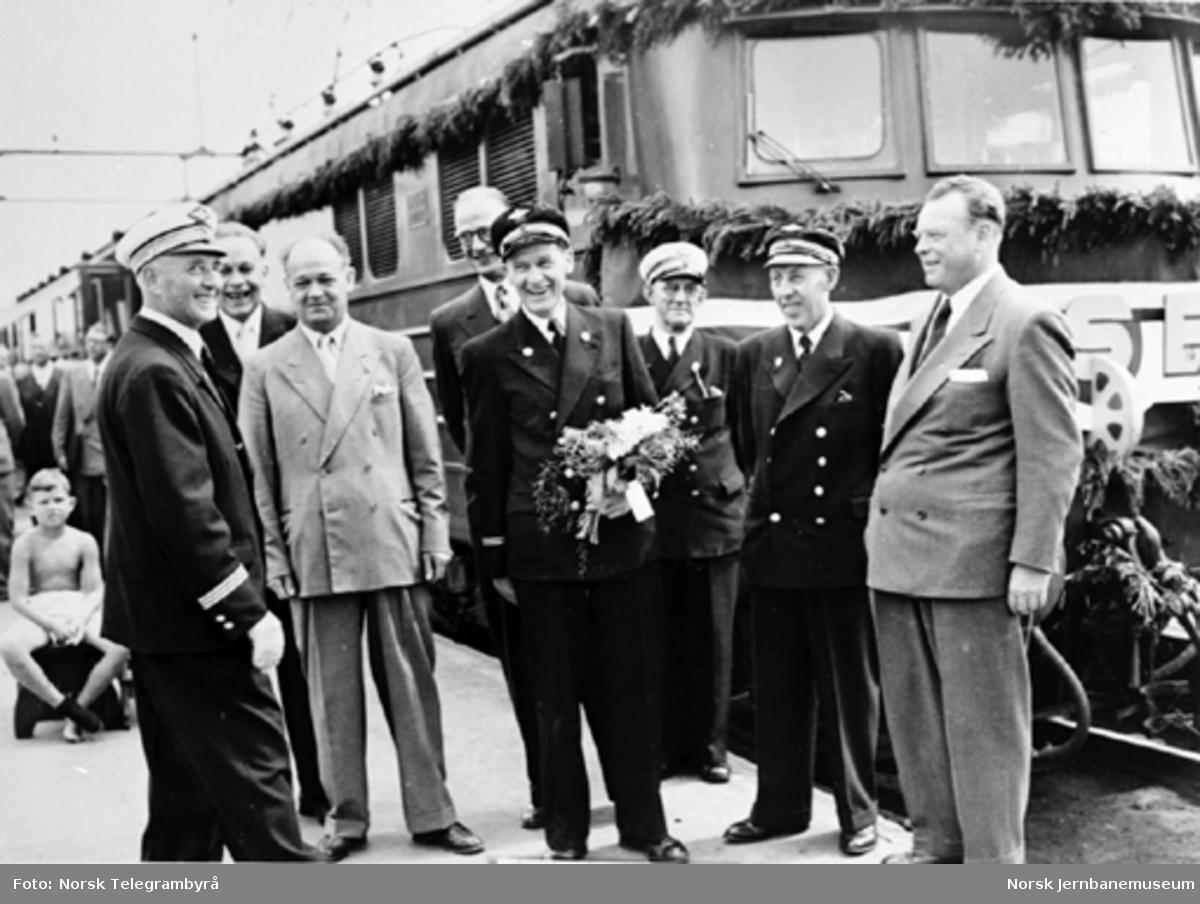 Lokomotivfører Ansten Kraft-Lund med blomster flankert av stasjonsmester Jensen, jernbanedirektør Sveaass, samferdselsministeren, ordføreren, overkonduktør Kjosbakken, lokomotivfører Rua og NSBs generaldirektør som bivånere