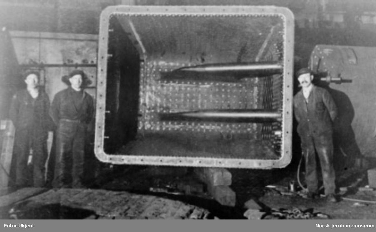 """Damplokomotiv type 49a """"Dovregubben"""" under bygging; tre arbeidere poserer med fyrkasse med syphoner (vannsirkulasjonsrør)"""