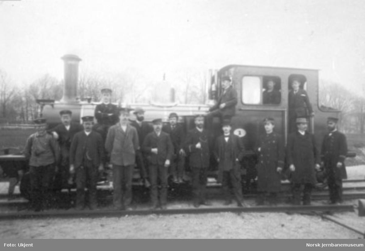 Gruppebilde av 16 jernbanefolk foran Setesdalsbanens damplokomotiv type XXI nr. 1