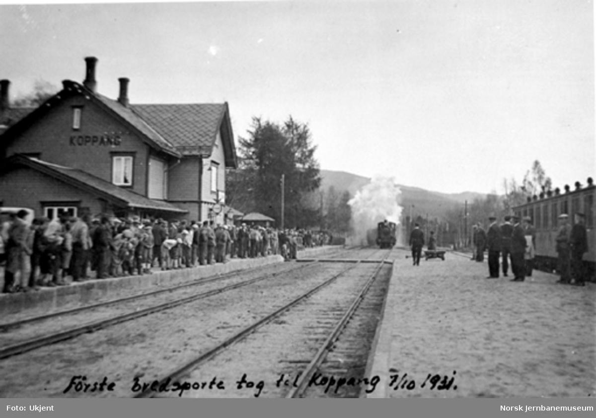 Det første normalsporede toget, tog 361, kjører inn på Koppang stasjon med en stor folkemengde på plattformen, en vogn i smalsportoget videre ses til høyre