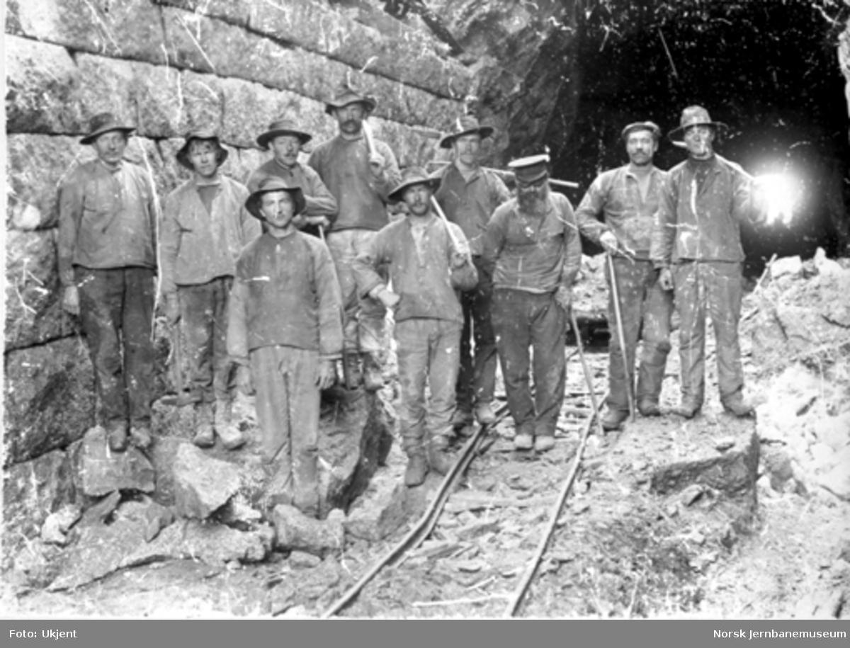 Anleggsarbeidere med spett ved siden av en gråsteinsmur og utenfor en tunnel