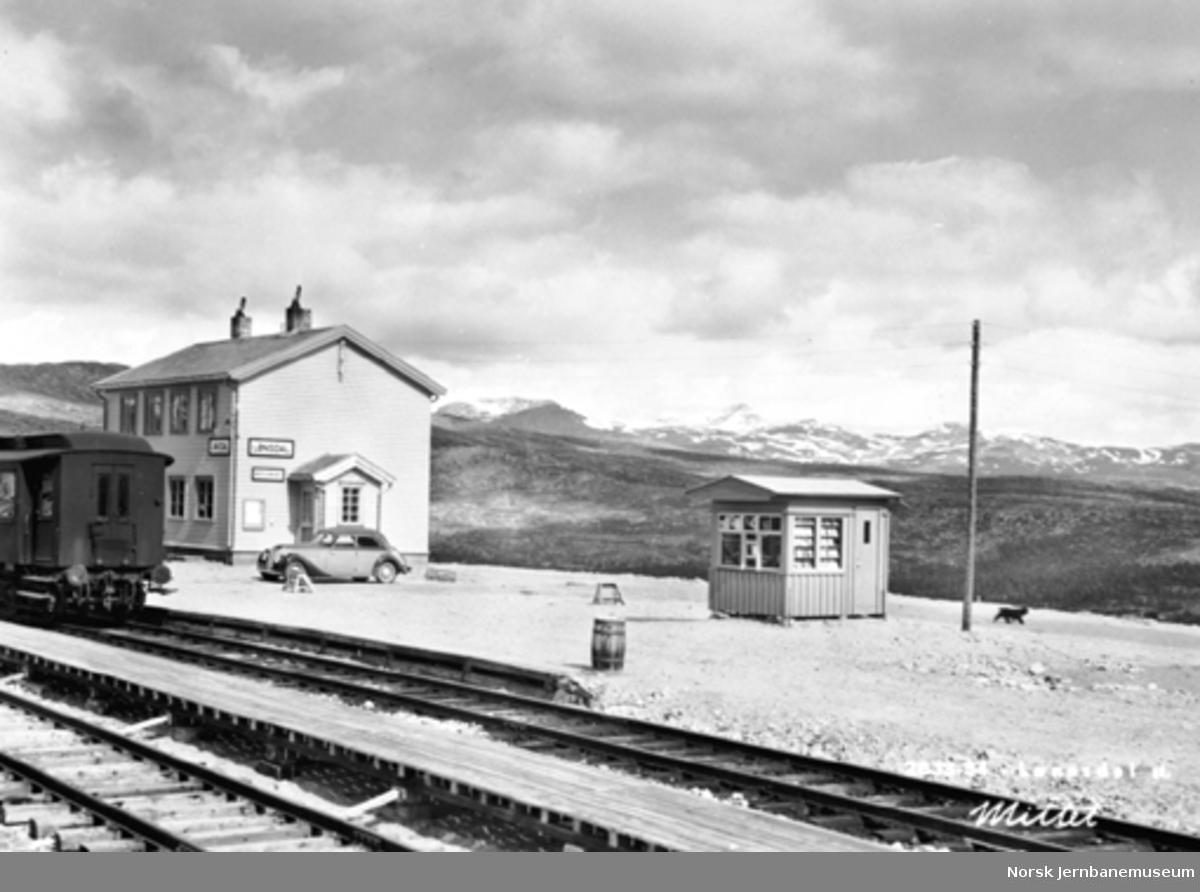 Lønsdal stasjon med stasjonsbygningen, kiosken og litt av en personvogn i spor 1
