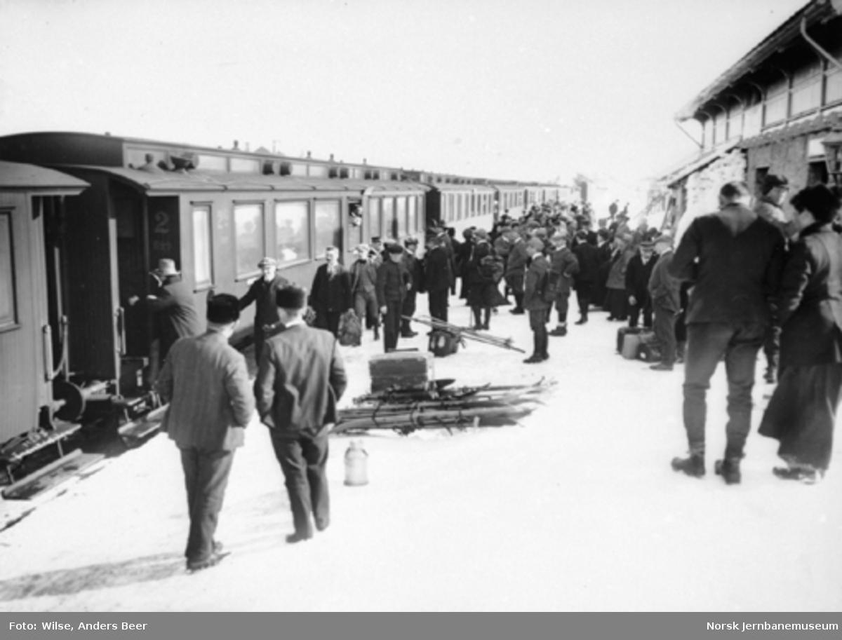 Påsketrafikk på Finse med reisende på plattformen og et persontog i spor 1