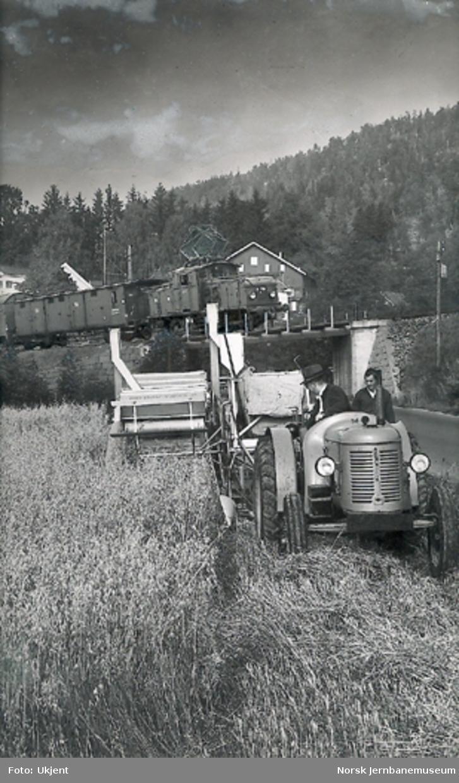 Fotomontasje med El 10 med godstog og en traktor med selvbinder i forgrunnen
