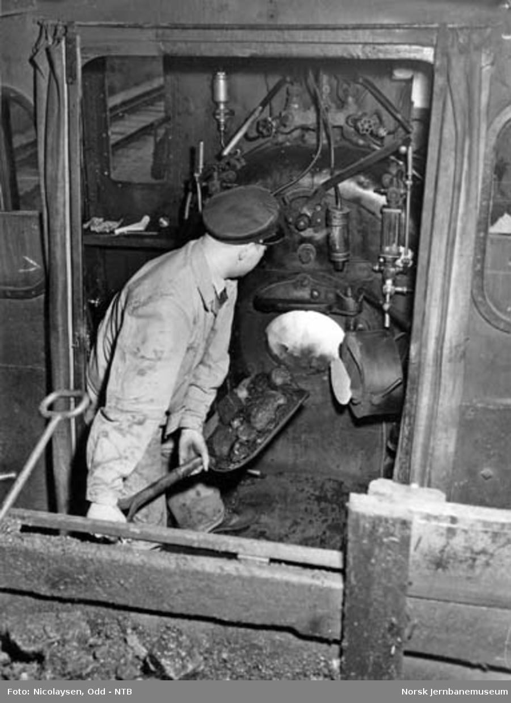 Interiørbilde fra førerhytte på et damplokomotiv med fyrbøteren i gang med å fyre
